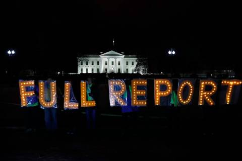 Members of the protest group Herndon Reston Indivisible and Kremlin Annex hold signs saying &qu ...