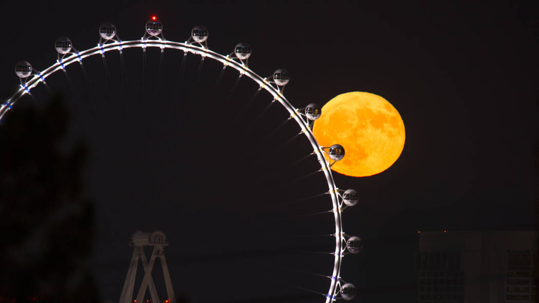 A full moon rises behind the High Roller observation wheel on the Strip in Las Vegas on Sunday, ...