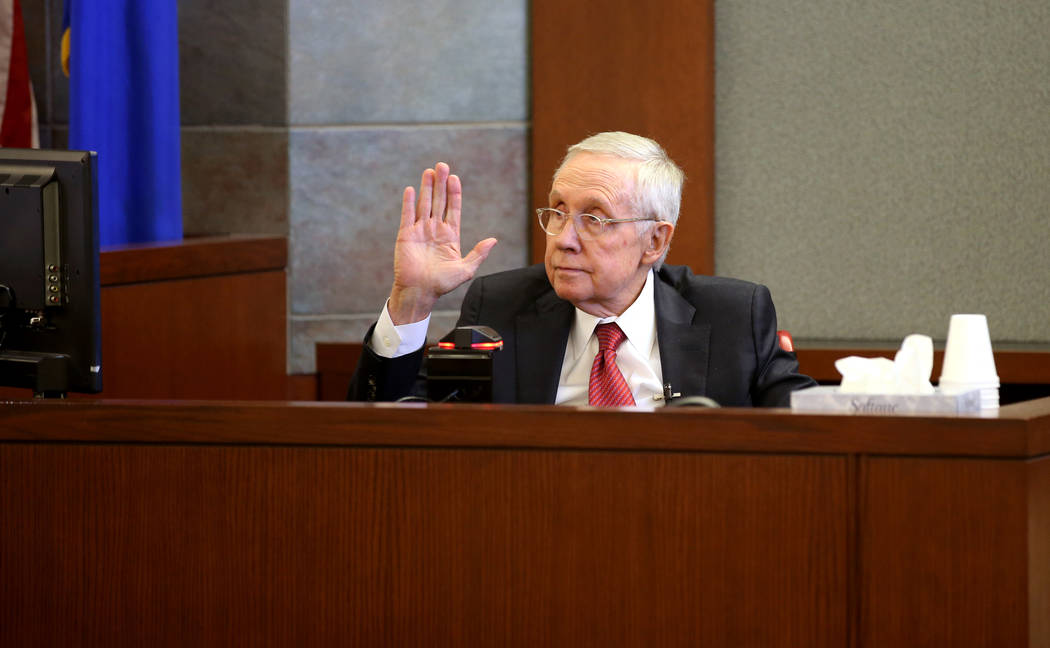 Former U.S. Sen. Harry Reid is sworn in on the witness stand at the Regional Justice Center in ...