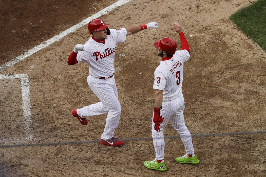 Philadelphia Phillies' Rhys Hoskins, left, celebrates his grand slam with Bryce Harper in the s ...