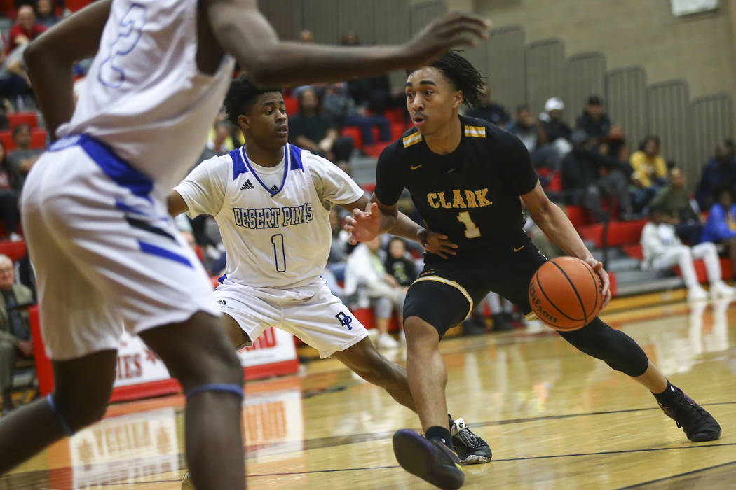 Clark's Frankie Collins (1) drives against Desert Pines' Semaj Threats (1) during the second ha ...
