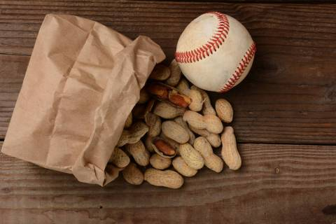 A bag of peanuts and a baseball on an old wooden bench at the ballpark. (Getty Images)