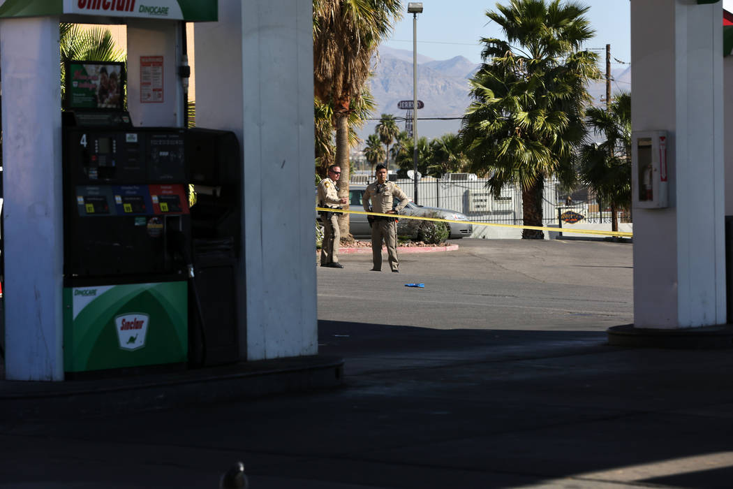 Las Vegas police officers block off a gas station at the corner of Washington Avenue and Las Ve ...