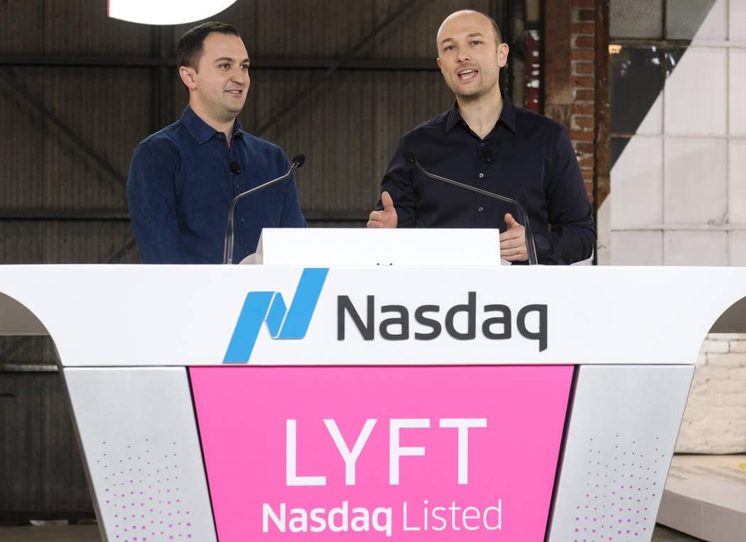 Lyft co-founder John Zimmer, left, listens as fellow co-founder Logan Green speaks before they ...