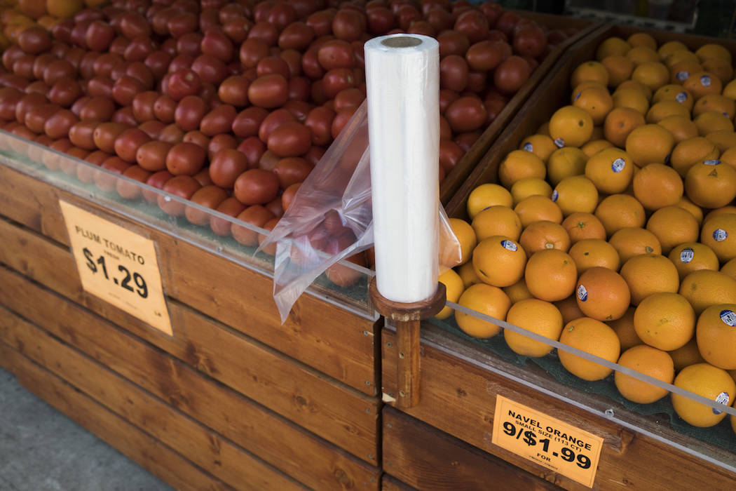 Oranges and tomatoes are seen on display for sale alongside a roll of plastic bags at a superma ...