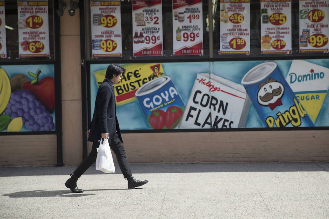 A man leaves a supermarket in the East Village neighborhood of Manhattan carrying his groceries ...