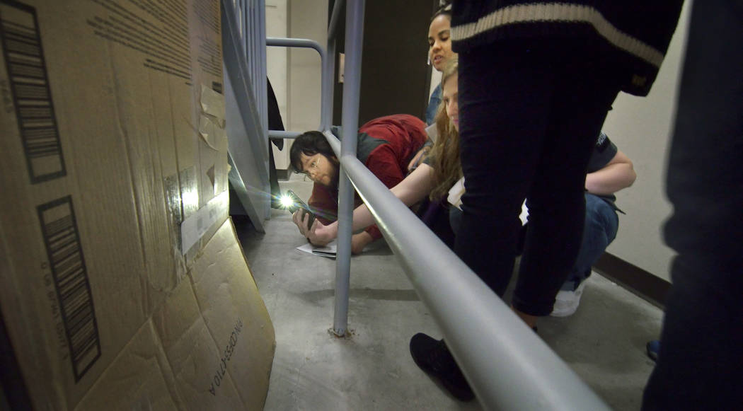 Students check out part of a crime scene during a simulated homicide investigation for a class ...