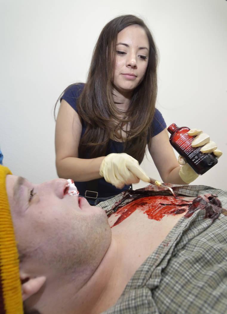 Makeup artist Jenny Egido puts some fake blood on actor Brice Johnson, playing a victim of poss ...