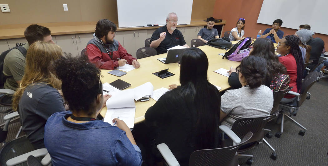 Lecturer Darwin Morgan, background center, talks with students during a briefing for a simulate ...