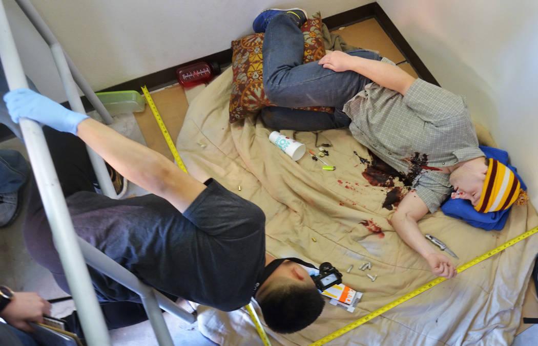 Student Richard Taitano, left, takes photos of evidence surrounding actor Brice Johnson, playin ...