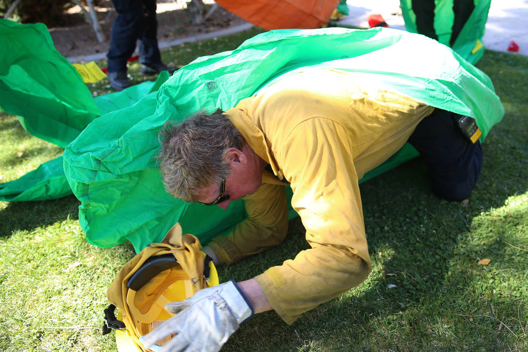Dennis Lovell, engine boss and firefighter at Mt. Charleston, takes cover under a fire shelter ...