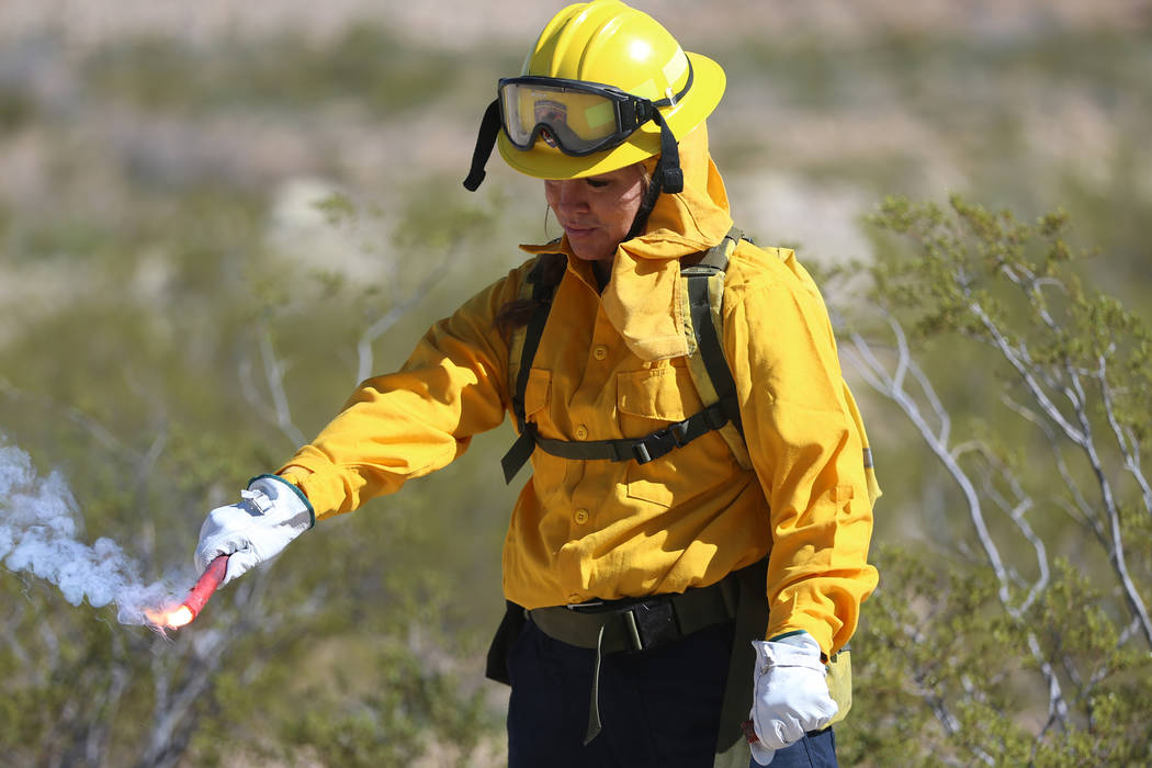 Heather Alexander, volunteer firefighter for Station 83 in Indian Springs, holds a fusee during ...