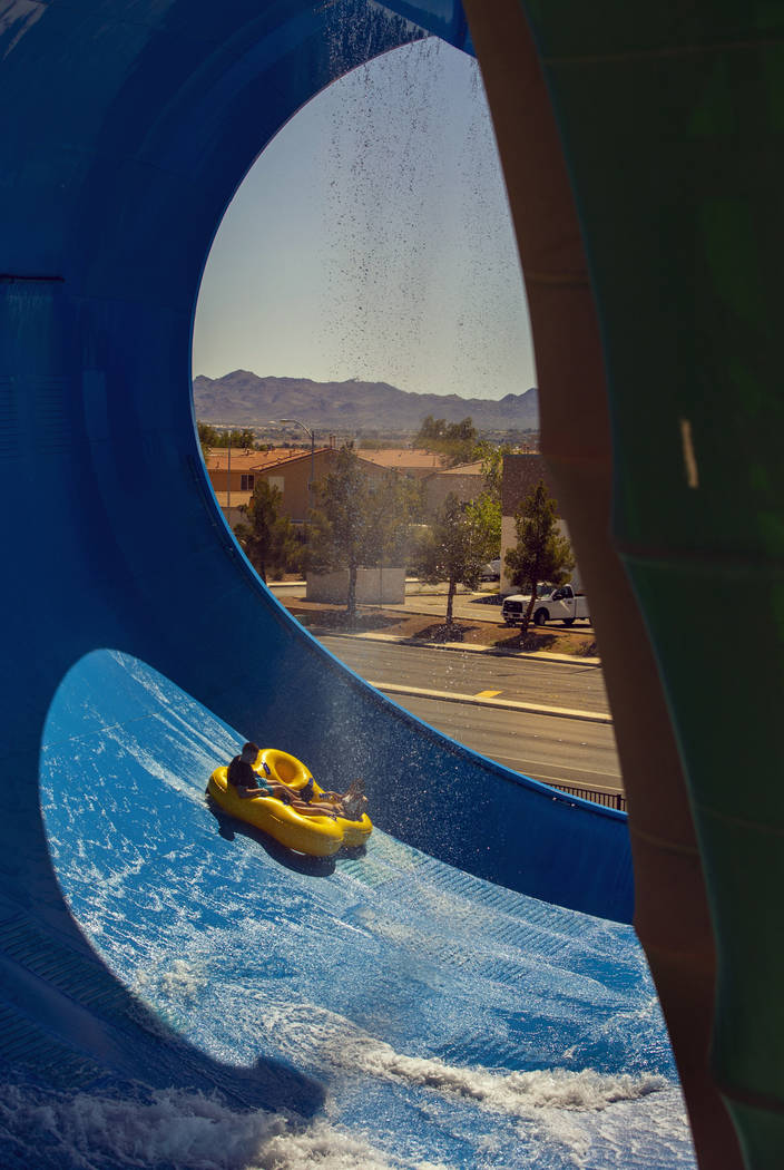 Riders raft down the wall of the Big Surf slide during opening day for the season at Cowabunga ...