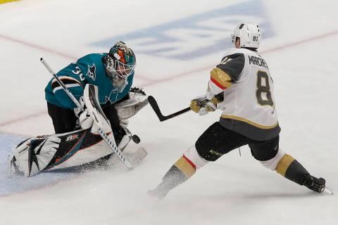 San Jose Sharks goaltender Aaron Dell, left, defends a shot attempt by Vegas Golden Knights cen ...