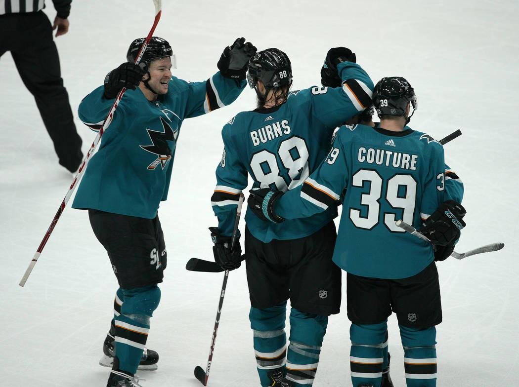 San Jose Sharks defenseman Brent Burns (88) celebrates with teammates Tomas Hertl, left, and Lo ...