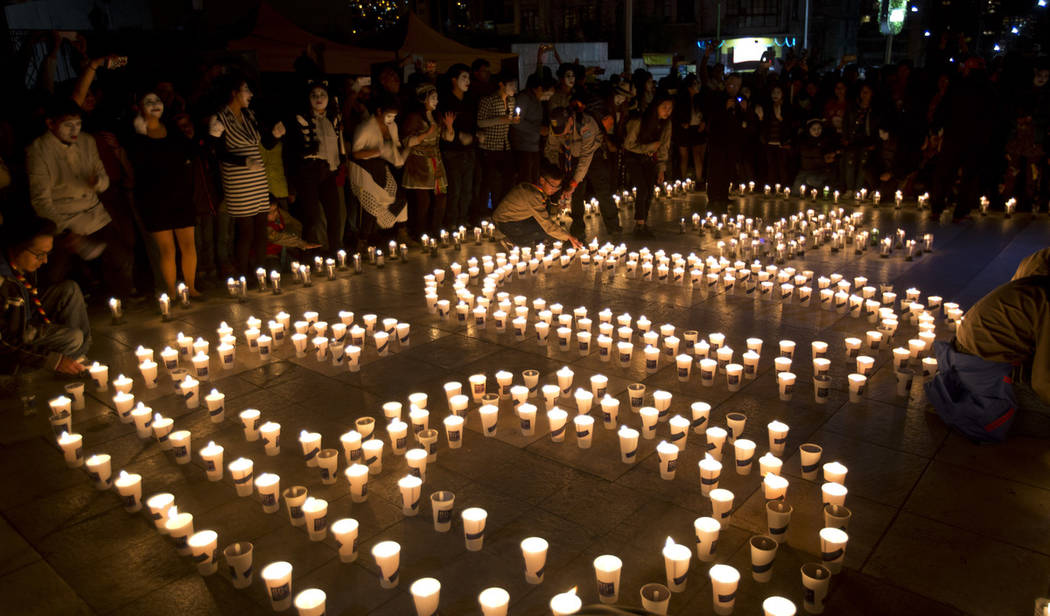 People gather near the arrangement of candles that form the number 60, to represent the minutes ...