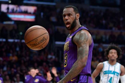 Los Angeles Lakers forward LeBron James, left, yells after dunking as Charlotte Hornets guard D ...