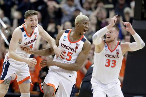Virginia's Mamadi Diakite, center, reacts with teammates Kyle Guy and Jack Salt (33) after hitt ...