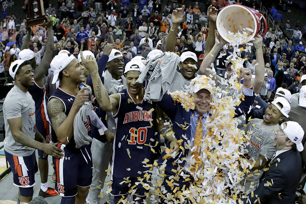 Auburn head coach Bruce Pearl is doused with confetti after the Midwest Regional final game aga ...