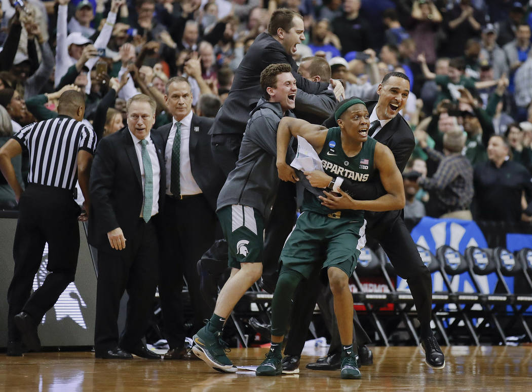 Michigan State guard Cassius Winston (5) begins to celebrate with members of his team after def ...
