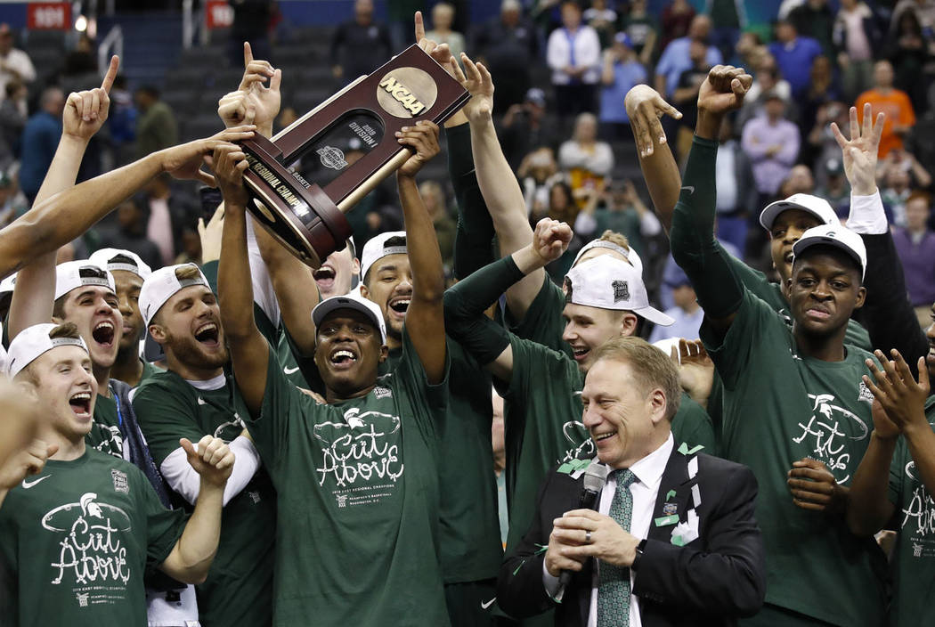 Michigan State guard Cassius Winston holds up the NCAA men's East Regional trophy as he celebra ...