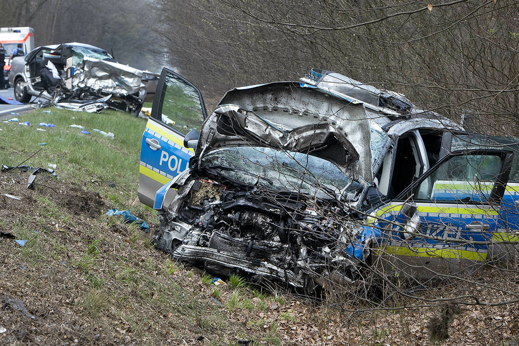 A damaged police car is seen next to a road in Langen near Frankfurt, Germany, Sunday, March 31 ...