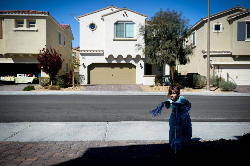 Madeline Brown, 3, rides a scooter outside of her house as her family hosts a yard sale in the ...
