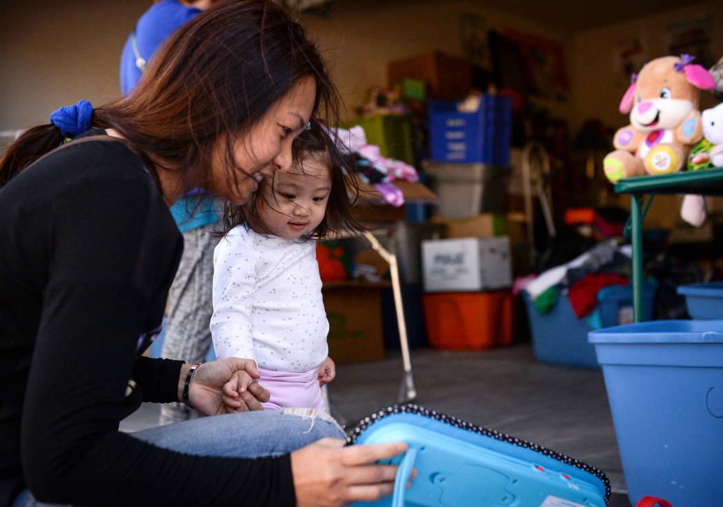 Aura Carreon, left, and her daughter, Ava Cruz, 1, from Las Vegas look through various items at ...
