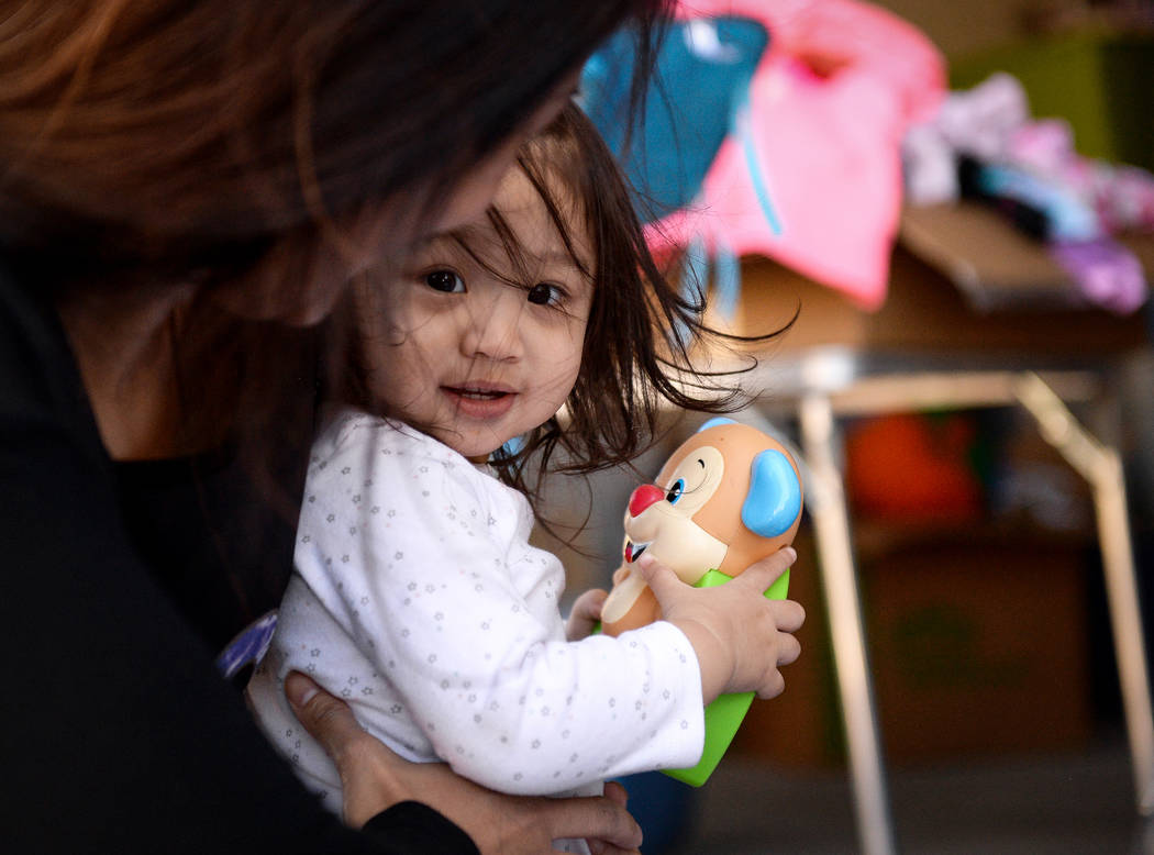 Ava Cruz, 1, holds an item she found at a yard sale while being held by her mother, Aura Carreo ...