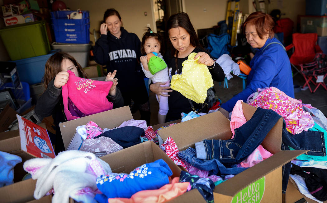 Aura Carreon, center, and her daughter, Ava Cruz, 1, from Las Vegas look through various items ...