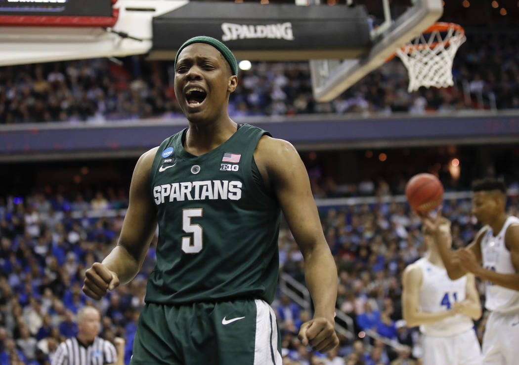 Michigan State guard Cassius Winston (5) reacts to scoring on Duke during the first half of an ...