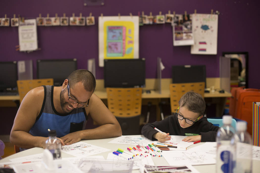 Joe Sheperd draws with Sterling Gylstorff, 8, at the Trans Day of Visibility event at The Cente ...