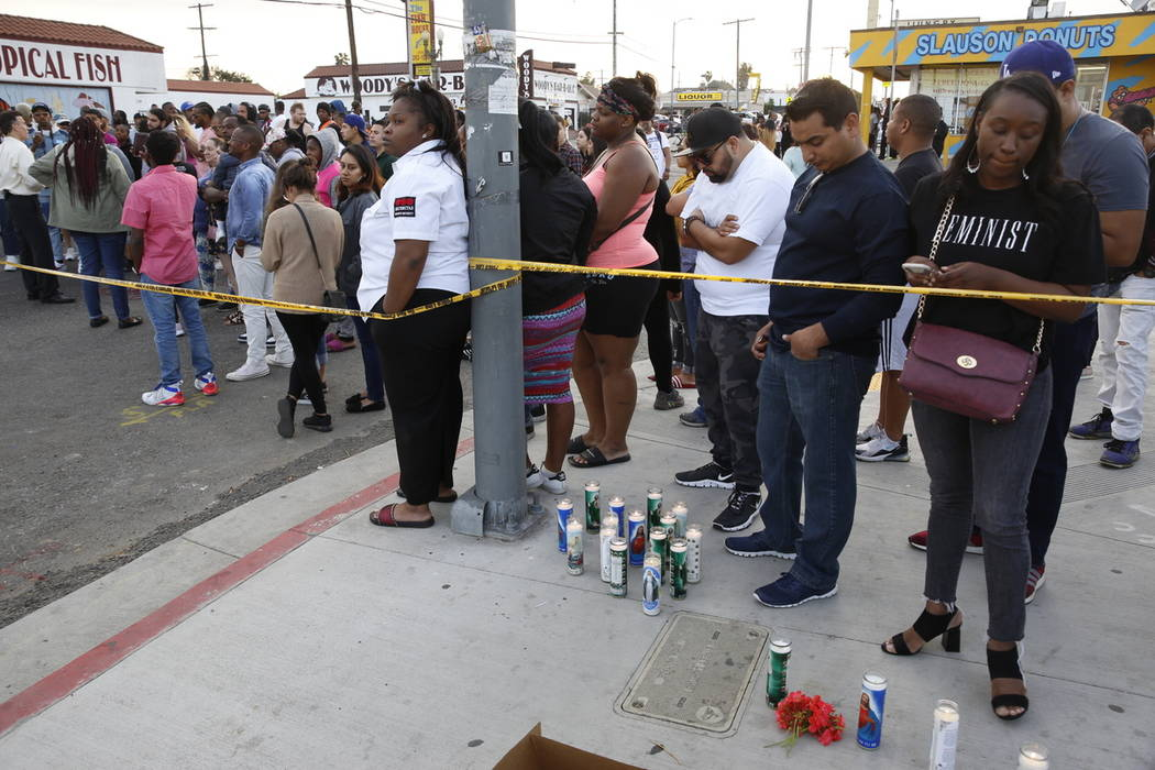 People set candles behind police yellow tape next to the Marathon Clothing store of rapper Nips ...