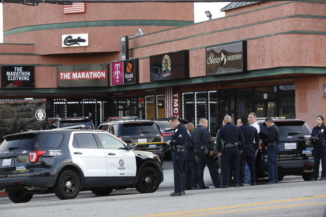 Police investigators gather around the Marathon Clothing store of rapper Nipsey Hussle in Los A ...