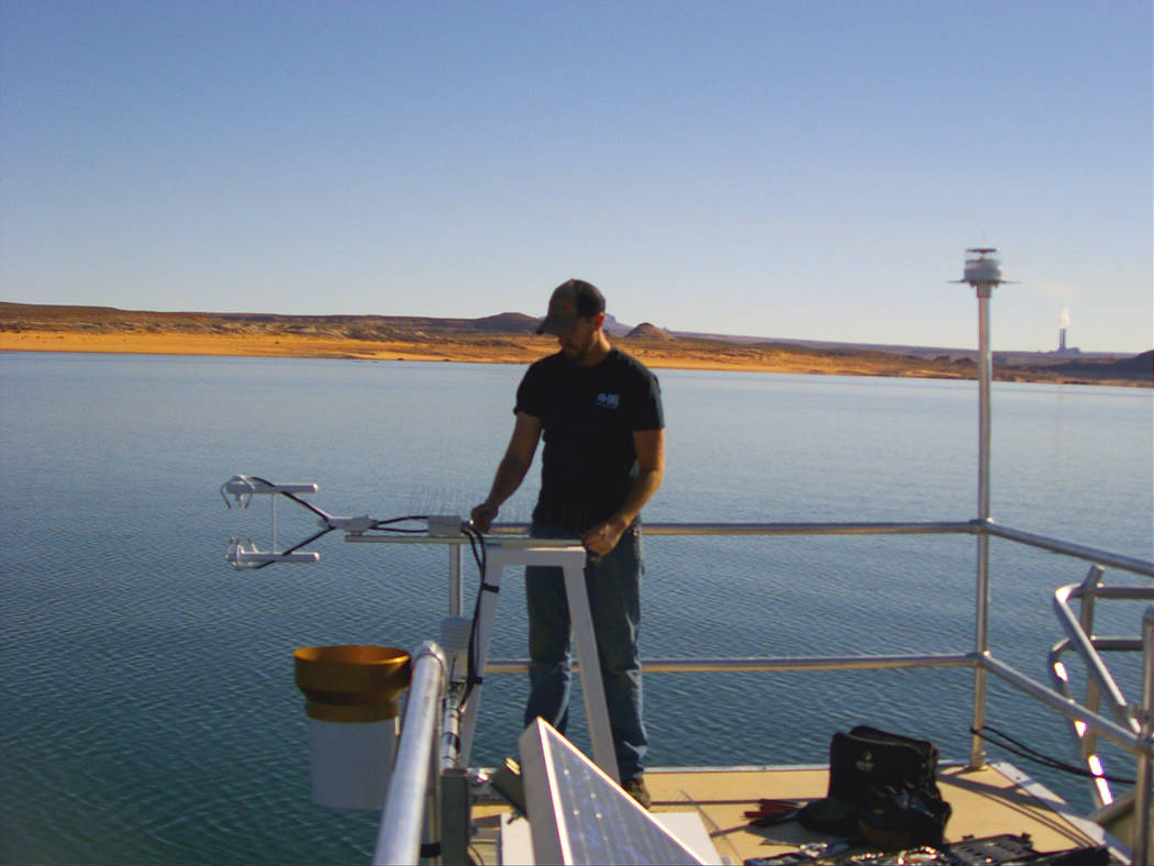 A researcher adjusts equipment during installation of a floating evaporation station at Lake Po ...