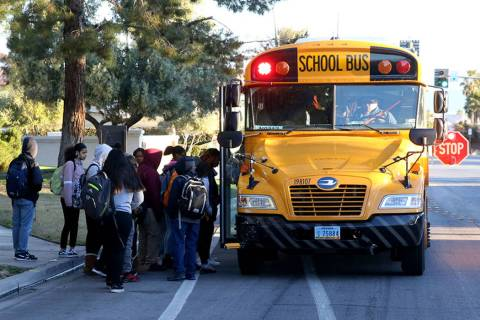 Students board the school bus on Soaring Gulls Drive near Cheyenne Avenue at Desert Shores Vill ...