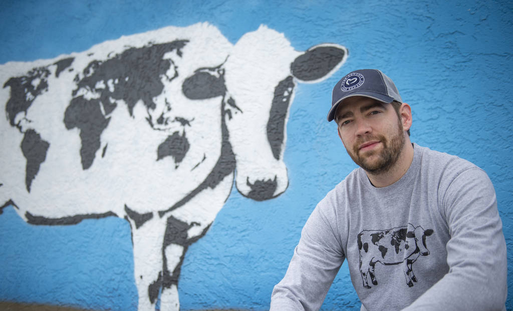 DJ Barry poses for a portrait in front of his mural located on the wall of Main Street Peddlers ...