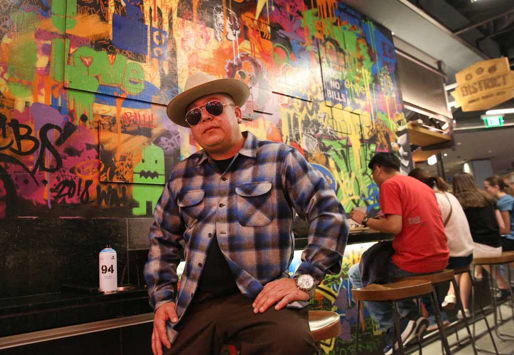 Tiki Jay One, an Urban Landscapist/Commercial Designer, poses for a photo in front of the mural ...