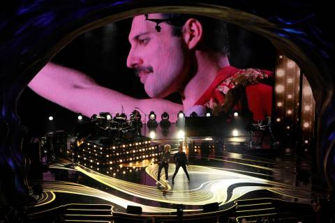 An image of Freddie Mercury appears on screen as Brian May, left, and Adam Lambert of Queen per ...