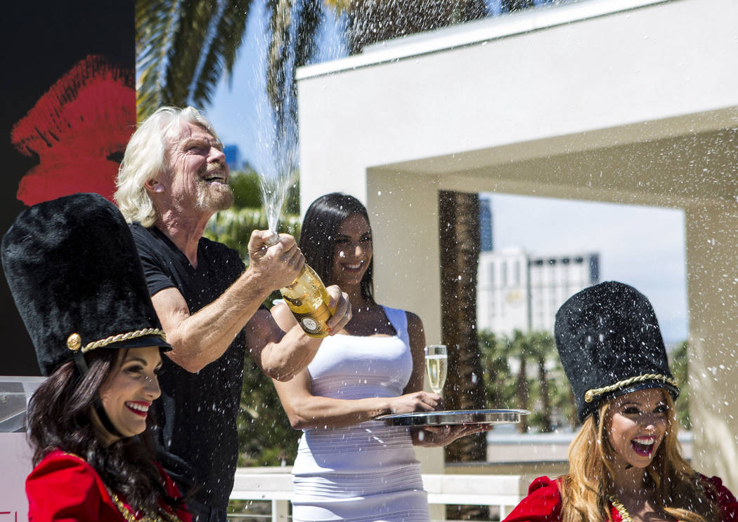 Virgin Group Founder Sir Richard Branson pops a champagne bottle following a press conference a ...