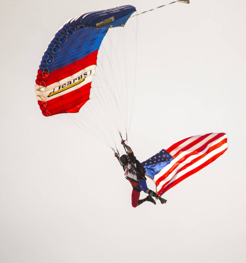 A parachuter arrives with the American flag during the NHRA Mello Yellow Drag Racing Series on ...