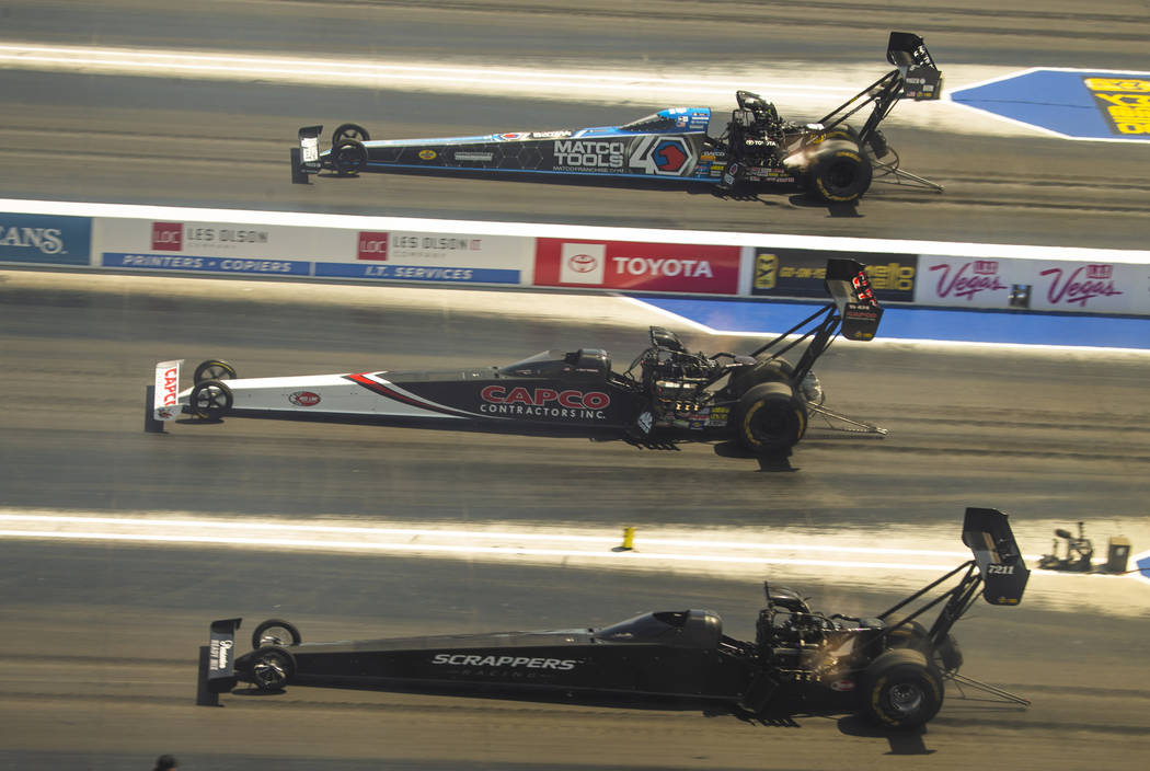 (From bottom) Top Fuel racers Mike Salinas, Billy Torrence and Antron Brown move down the track ...