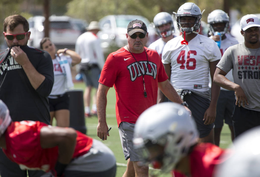 UNLV football coach Tony Sanchez watches over his players as they runs through drills during te ...