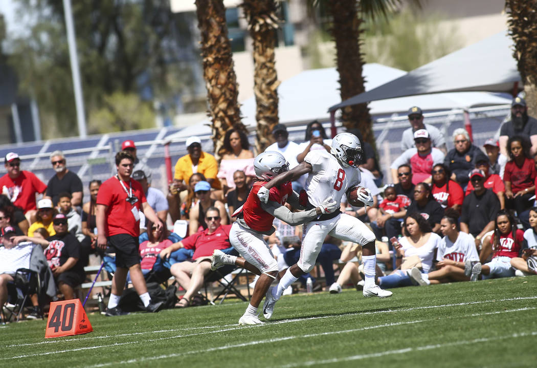 UNLV Rebels running back Charles Williams (8) runs the ball under pressure from defensive back ...