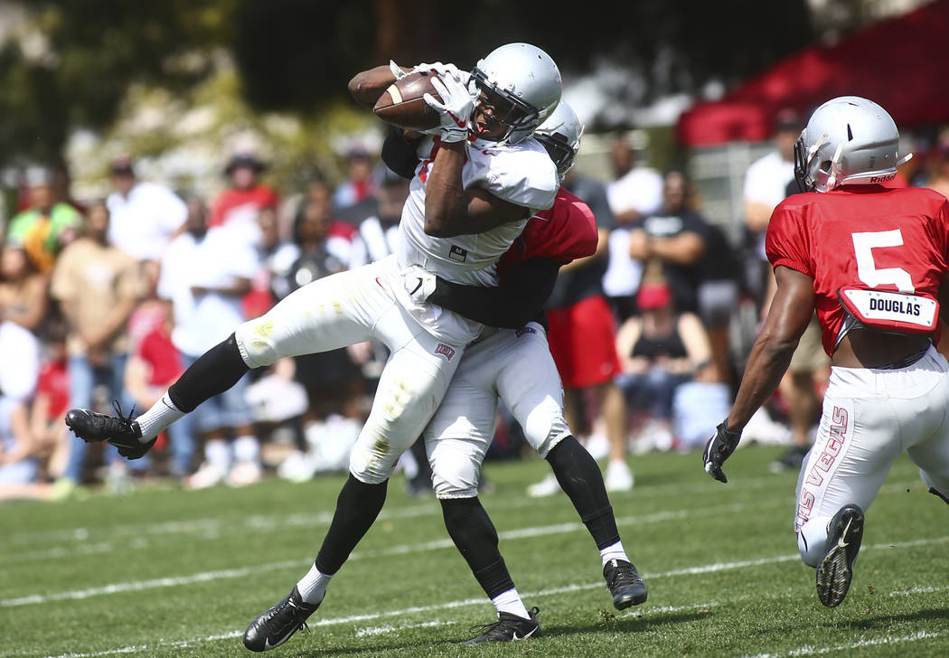 UNLV Rebels wide receiver Jeremy Clark (18) keeps hold of a reception under pressure from defen ...