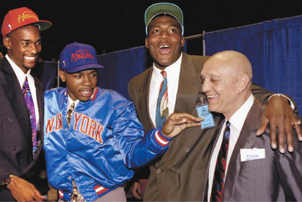 University of Nevada-Las Vegas coach Jerry Tarkanian celebrates with three of his Runnin' Rebel ...