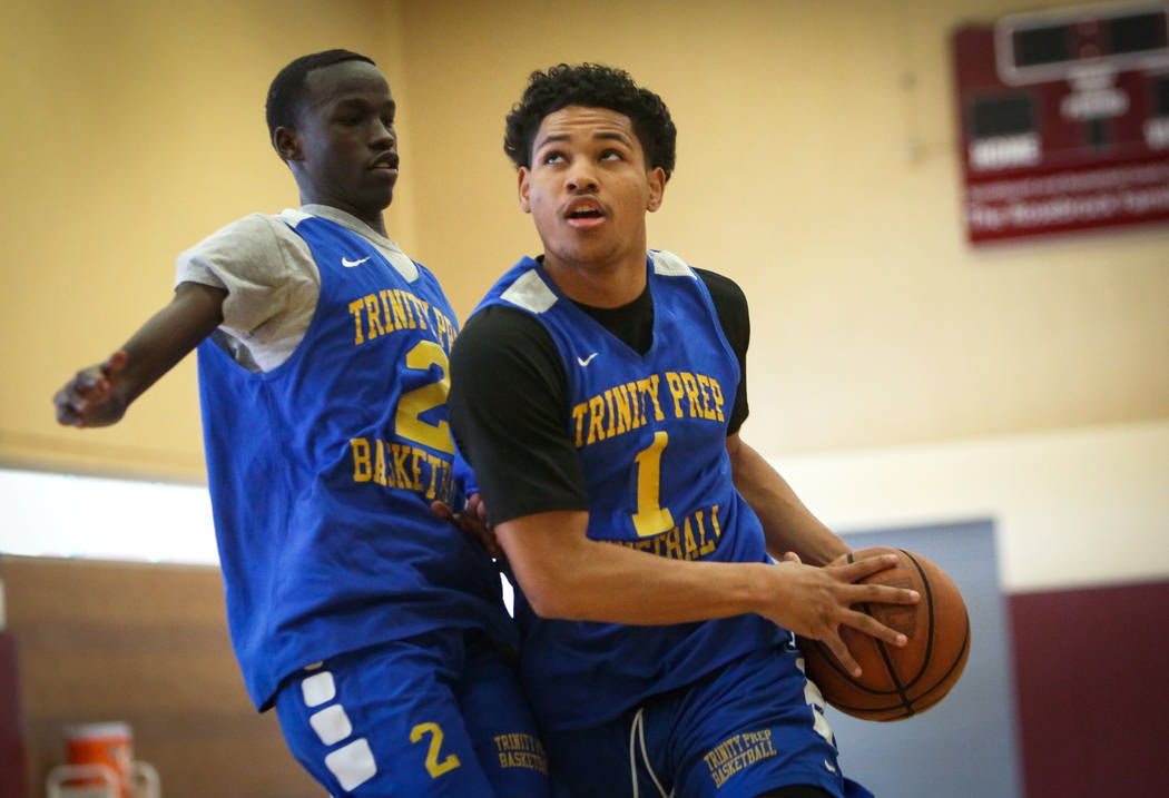 Trinity International junior Daishen Nix, right, drives past teammate Madait Mou during a pract ...