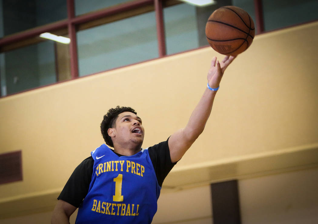 Trinity International junior Daishen Nix reaches for the ball during a practice at the Bill and ...