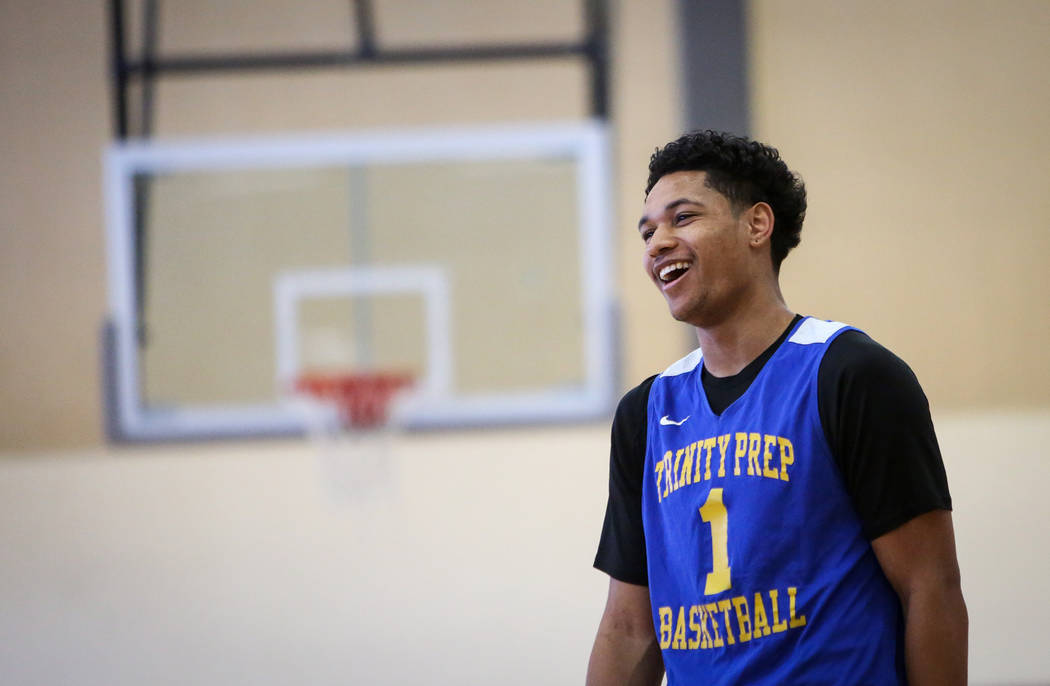 Trinity International junior Daishen Nix laughs while talking with his teammates during a pract ...