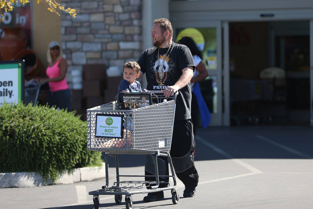 Tom Brown with his nephew Timmy Brown walk to their car after shopping at Smith's, 10600 Southe ...